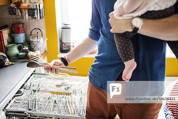 Mann tragen Mittlerer Ausschnitt Küche ausleeren Spülmaschine Baby