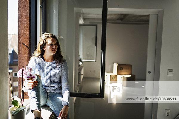 sitzend Frau sehen Fenster wegsehen Reise Nachdenklichkeit Fensterbank Eigentumswohnung neues Zuhause