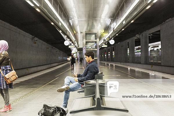 sitzend benutzen Mann Plattform Ansicht Seitenansicht Smartphone Zug Haltestelle Haltepunkt Station