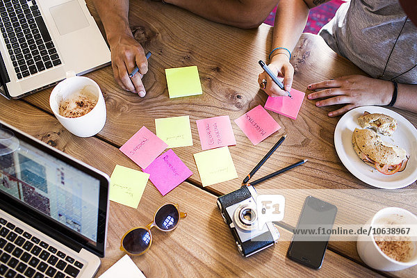 hoch oben Freundschaft schreiben arbeiten Cafe Ansicht Flachwinkelansicht Klebstoff Winkel