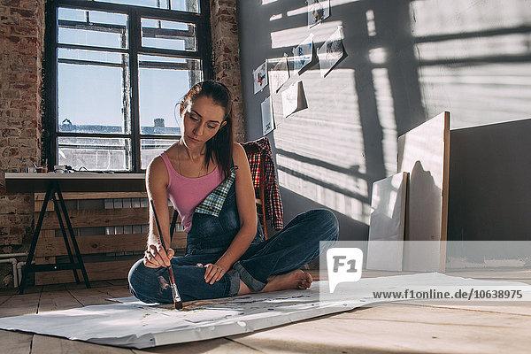 Frau beim Malen im Atelier auf dem Boden sitzend