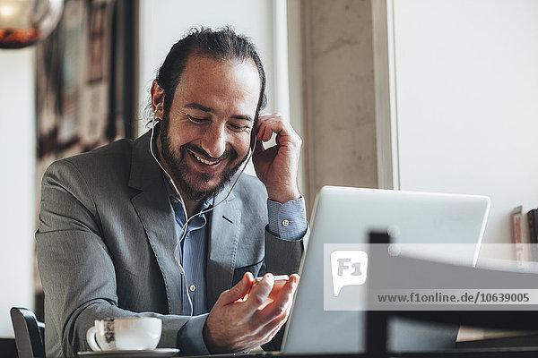 Fröhlicher Geschäftsmann  der Musik über Handy im Café hört.