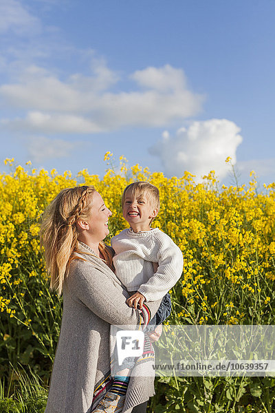 Frau Fröhlichkeit tragen Sohn Feld Raps Brassica napus