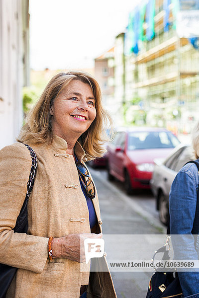 Senior woman standing with friends at street