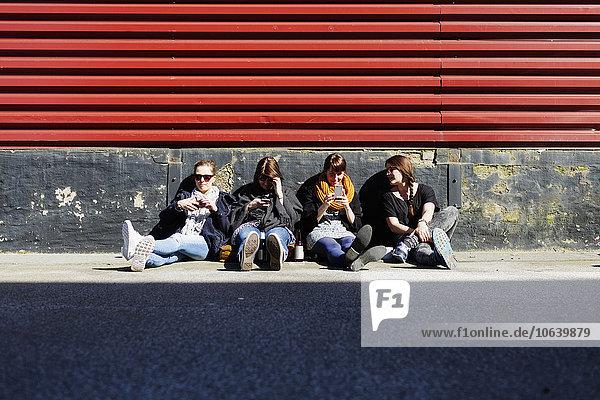 Friends using smart phones on street