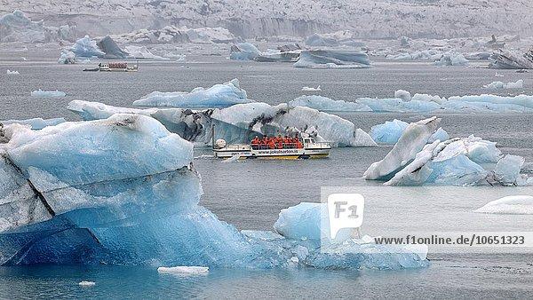 Treibende blaue Eisberge in der Gletscherlagune Jökulsarlon mit Touristenbooten  hinten der Gletscher Vatnajökull  Südisland  Island  Europa