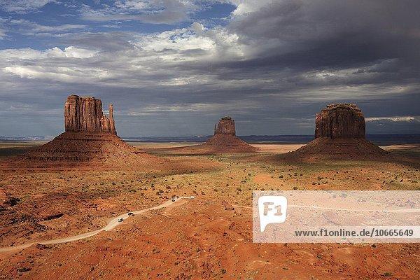 Felsformationen  West Mitten Butte  East Mitten Butte und Merrick Butte  vorne Valley Drive  nach einem Gewitter  Gewitterwolken  Abendlicht  Monument Valley Navajo Tribal Park  Arizona  USA  Nordamerika