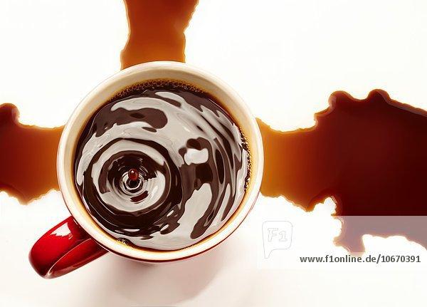 fallen fallend fällt Tasse weiß schwarz Schmutzfleck heraustropfen tropfen undicht hoch oben Hintergrund rot Ansicht Kaffee