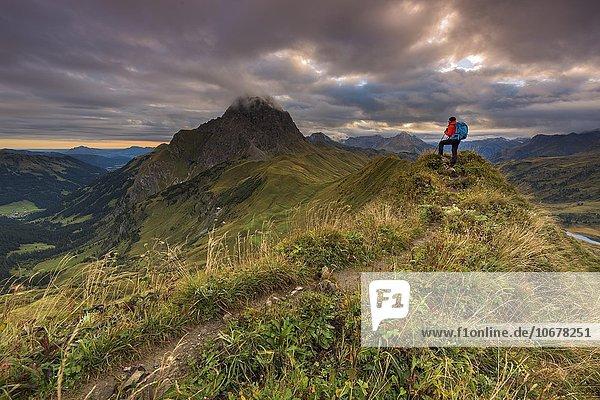 Bergsteiger blickt auf Gipfel des Widderstein  Allgäuer Alpen  Wolkenstimmung am Morgen  Warth  Vorarlberg  Österreich  Europa