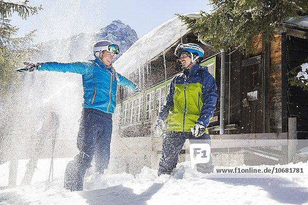 Skifahrer mit Helmen machen eine Pause vor einer Hütte und haben Spaß im Schnee  Mutterer Alm  Mutters  Tirol  Österreich  Europa