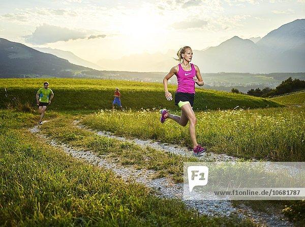 Junge Frau  20-25 Jahre  läuft auf einem Weg durch Wiesen  hinten weitere Läufer  Rosengarten  Patsch  Tirol  Österreich  Europa