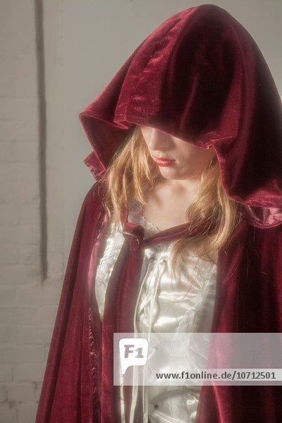 Blonde teenage girl wearing a robe with a hood.