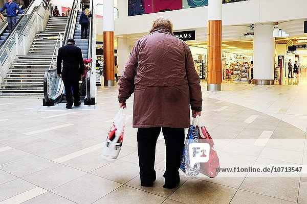 A tired  elderly shopper in a shopping mall.
