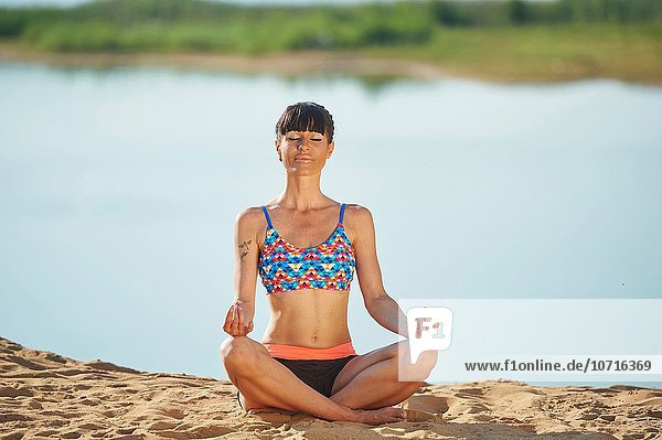 Young woman doing yoga on a beach next to a little lake.