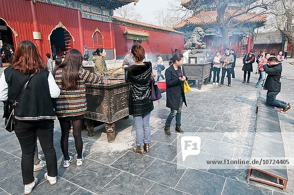 Group of chinese people burning incenses in Yonghe Temple also known as Lama Temple.
