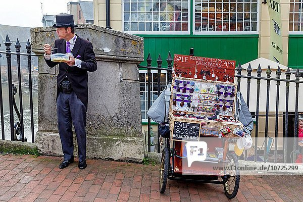 A Well Dressed Man Eating Lunch and Selling Items From A Mobile Stall  High Street  Lewes  Sussex  UK.