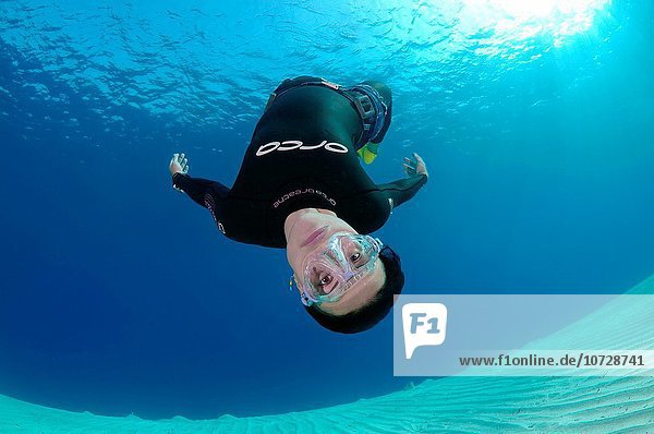 Freediver swims over a sandy bottom  Red Sea  Egypt.