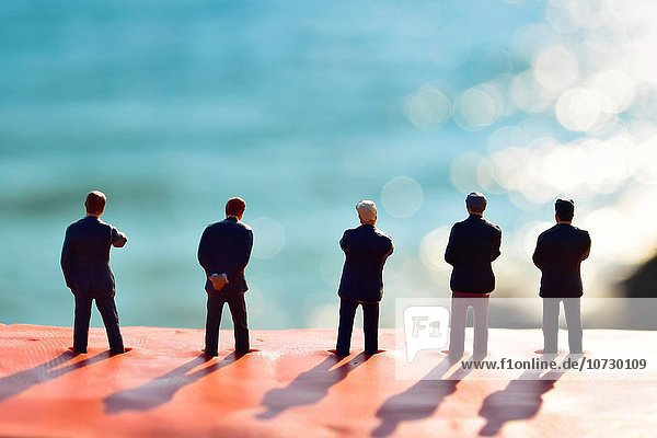 Figurines of businessmen watching a blurred landscape. Toy businessmen team  silhouettes of men against blurred sea.