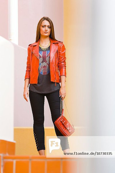Young woman fanciful in Red jacket with purse in hand