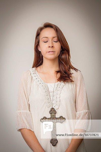junge Frau junge Frauen überqueren groß großes großer große großen Kleidung Kreuz Metall