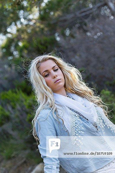 Beautiful blonde countrygirl n denim shirt waist-up shot.