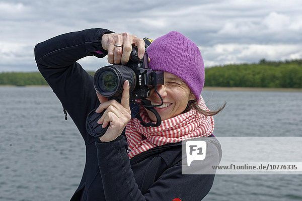 Woman photographing  Mecklenburg Lake District  Brandenburg  Germany  Europe