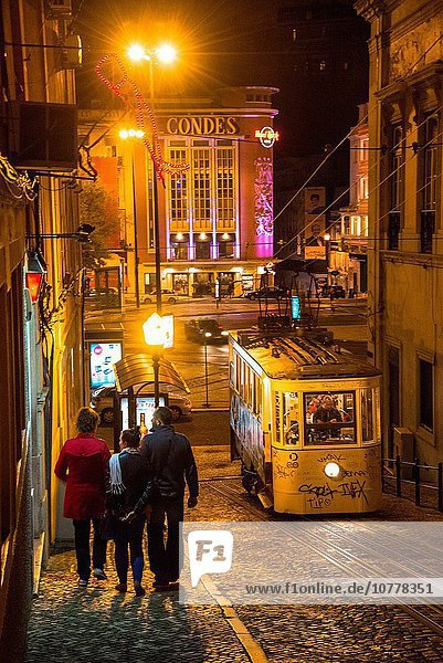 Night view at tram and hard rock cafe from hilly street in lisboa portugal