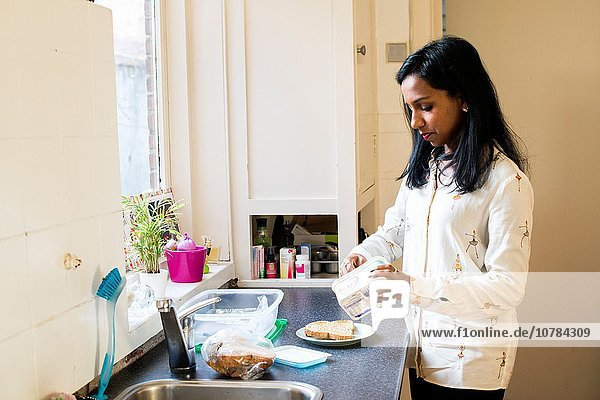 Tilburg  Netherlands. Young  dark skinned woman doing the dishes after lunch  inside her kitchen at home.