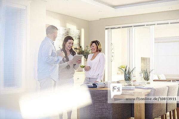 Innenarchitektin mit digitalem Tablett in Absprache mit dem Paar im Esszimmer