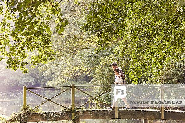 Vater und Sohn überqueren Fußgängerbrücke im Park mit Bäumen
