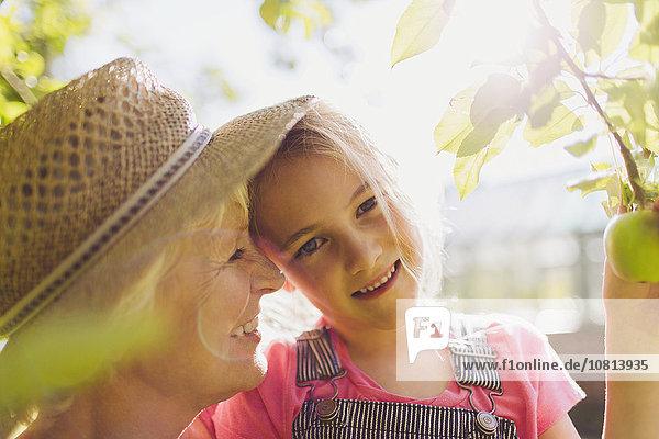 Portrait lächelnde Enkelin mit Großmutter im sonnigen Garten
