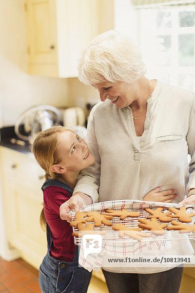 Enkelin umarmt Großmutter beim Backen von Lebkuchenkeksen