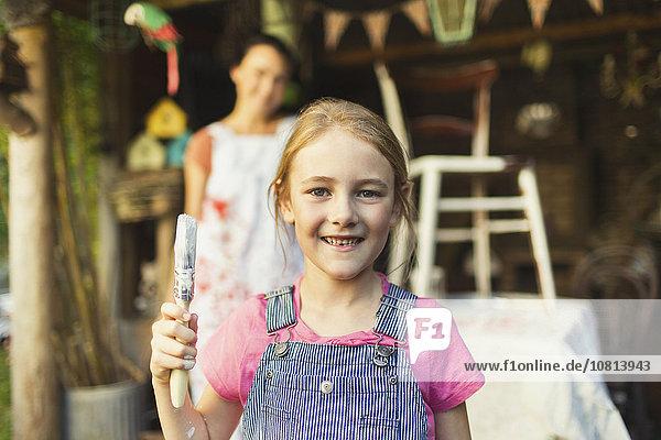 Portrait lächelndes Mädchen mit Pinsel in der Hand