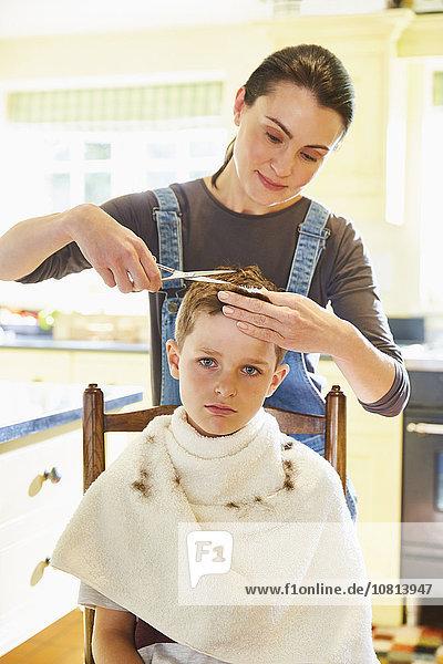 Porträt eines unglücklichen Jungen  der sich von seiner Mutter in der Küche die Haare schneiden lässt.