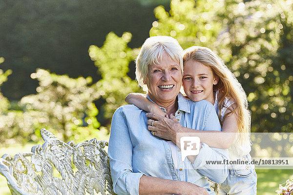 Portrait lächelnde Großmutter und Enkelin umarmend im Garten