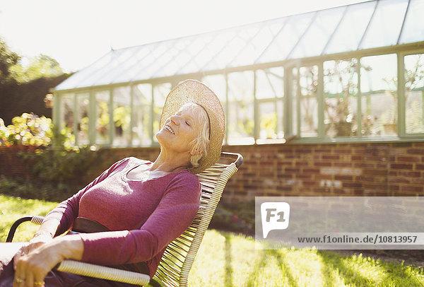 Sorgenfreie Seniorin entspannt sich vor dem sonnigen Gewächshaus