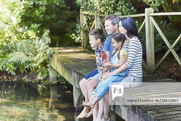 Familie sitzt am Rande des Hafens