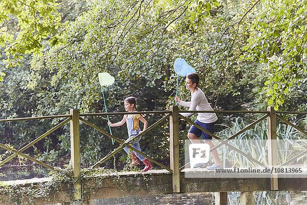 Geschwister laufen mit Schmetterlingsnetzen auf der Fußgängerbrücke im Park
