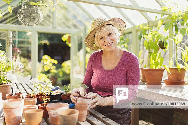 Portrait lächelnde Seniorin Topfpflanzen im Gewächshaus