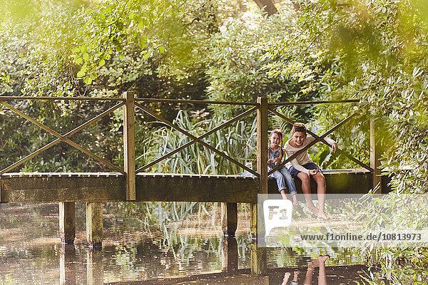Bruder und Schwester sitzen auf einer Fußgängerbrücke im Park mit Bäumen.