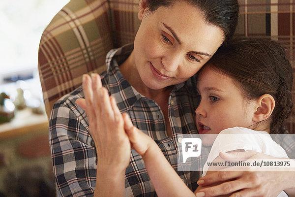 Zärtliche Mutter und Tochter halten sich an den Händen.