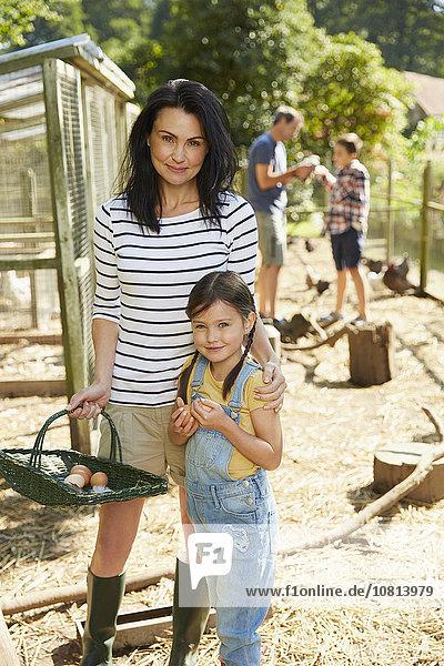 Portrait Mutter und Tochter mit Korb mit frischen Eiern außerhalb des Hühnerstalles