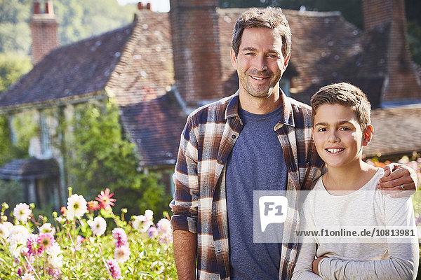 Portrait lächelnder Vater und Sohn im sonnigen Blumengarten