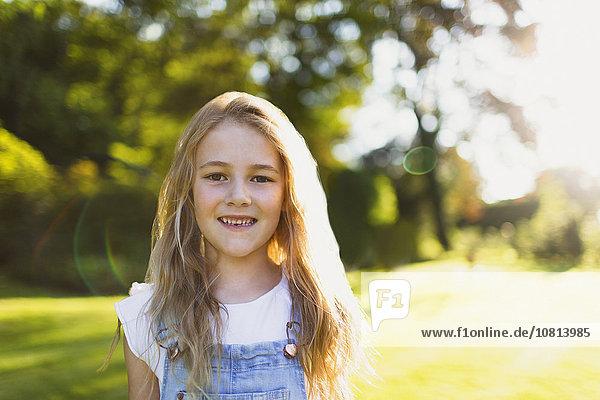 Portrait lächelndes Mädchen im sonnigen Garten
