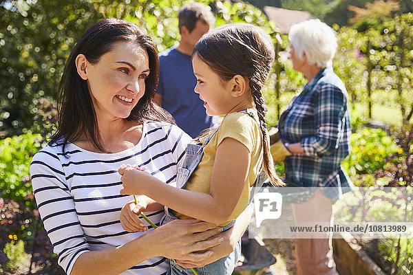 Zärtliche Mutter mit Tochter im sonnigen Garten