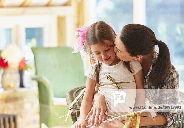 Mutter  die die Wange ihrer Tochter küsst.