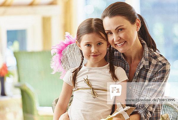 Portrait lächelnde Mutter und Tochter mit Flügeln