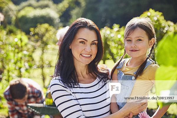 Portrait lächelnde Mutter und Tochter umarmend im sonnigen Garten