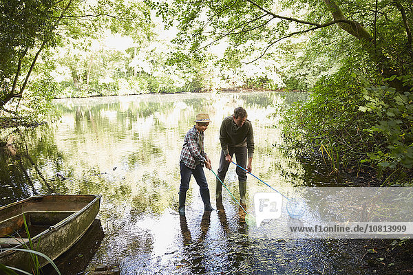 Vater und Sohn fischen mit Netzen im Waldteich