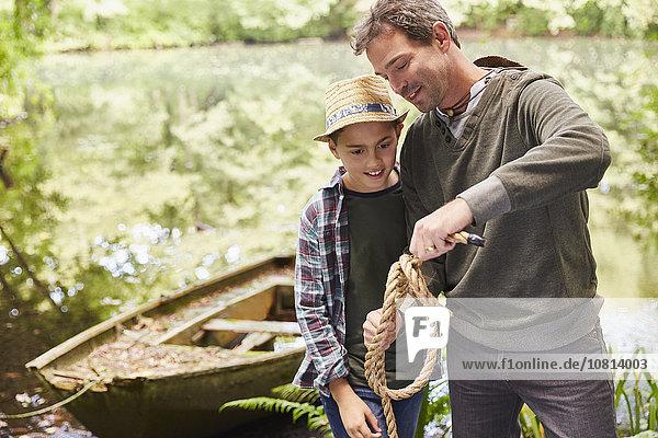 Vater lehrt den Sohn  wie man einen Seilknoten bindet.